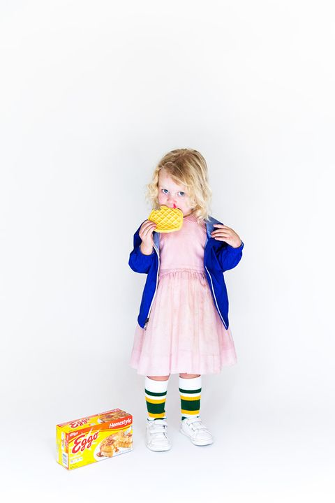 little blonde girl dressed as eleven from stranger things, with a bloody nose, eating an eggo waffle with an eggo box beside her, in a pink dress with athletic socks and a blue hoodie