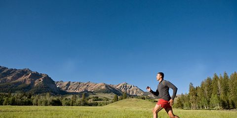 Guy Runner Running Past Mountains and Trees