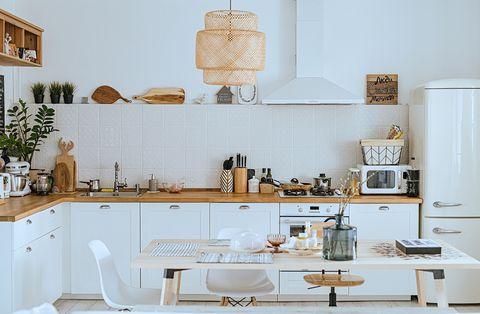 scandinavian style cozy modern kitchen interior with a dining zone, white modern interior, everyday still llife, stay at home coronavirus quarantine, chores