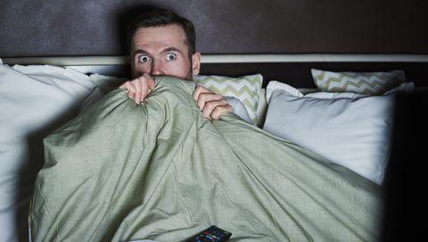 man kijkt horror in bed