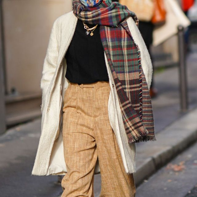 paris, france   january 28 a passerby wears a face mask, a green and brown checked fringed wool scarf, a black pullover, a golden necklace, a white wool long jacket, brown pants, on january 28, 2021 in paris, france photo by edward berthelotgetty images