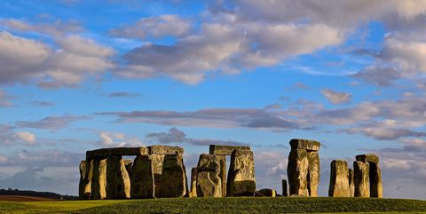 Scenic View Of Stonehenge In Field Against Cloudy Sky