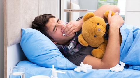 Man met mannengriepligt in bed met teddybeer