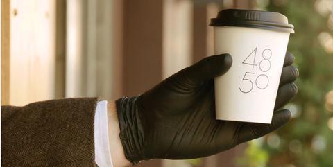 Een hand die een koffiebeker van4850 vasthoudt