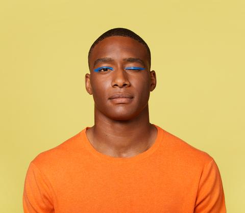 jonge man knipoogt met blauwe eyeliner