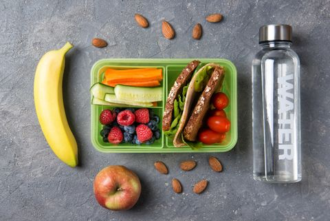 School lunch box with sandwich, vegetables, fruits and water on black background, healthy eating concept, top view
