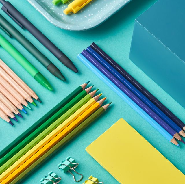 pens, pencils and binder clips on blue background