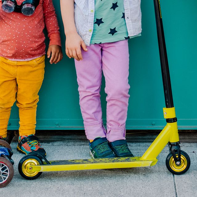 kids with scooters on sidewalk