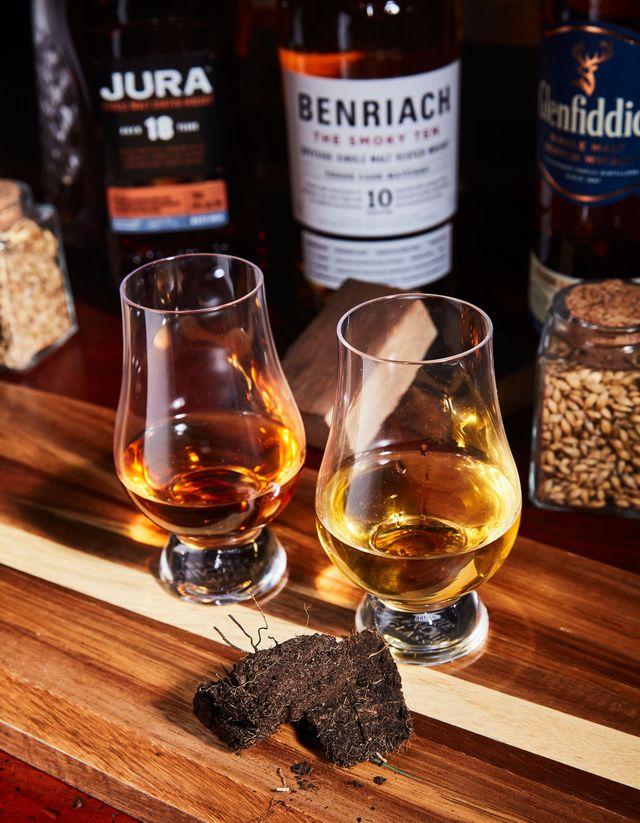 scotch in two glencairn glasses next to peat