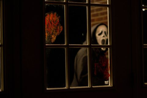 ghostface en scream 4 con una puerta con una huella de sangre