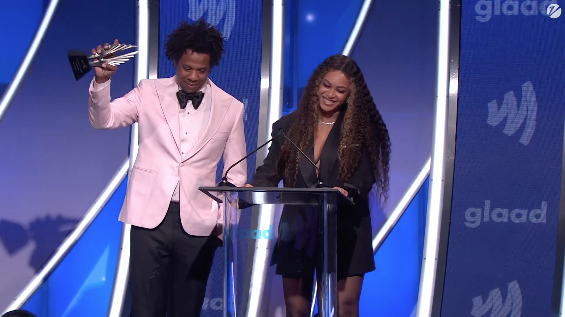 Jay-Z accepts a GLAAD award in a pink dinner jacket.