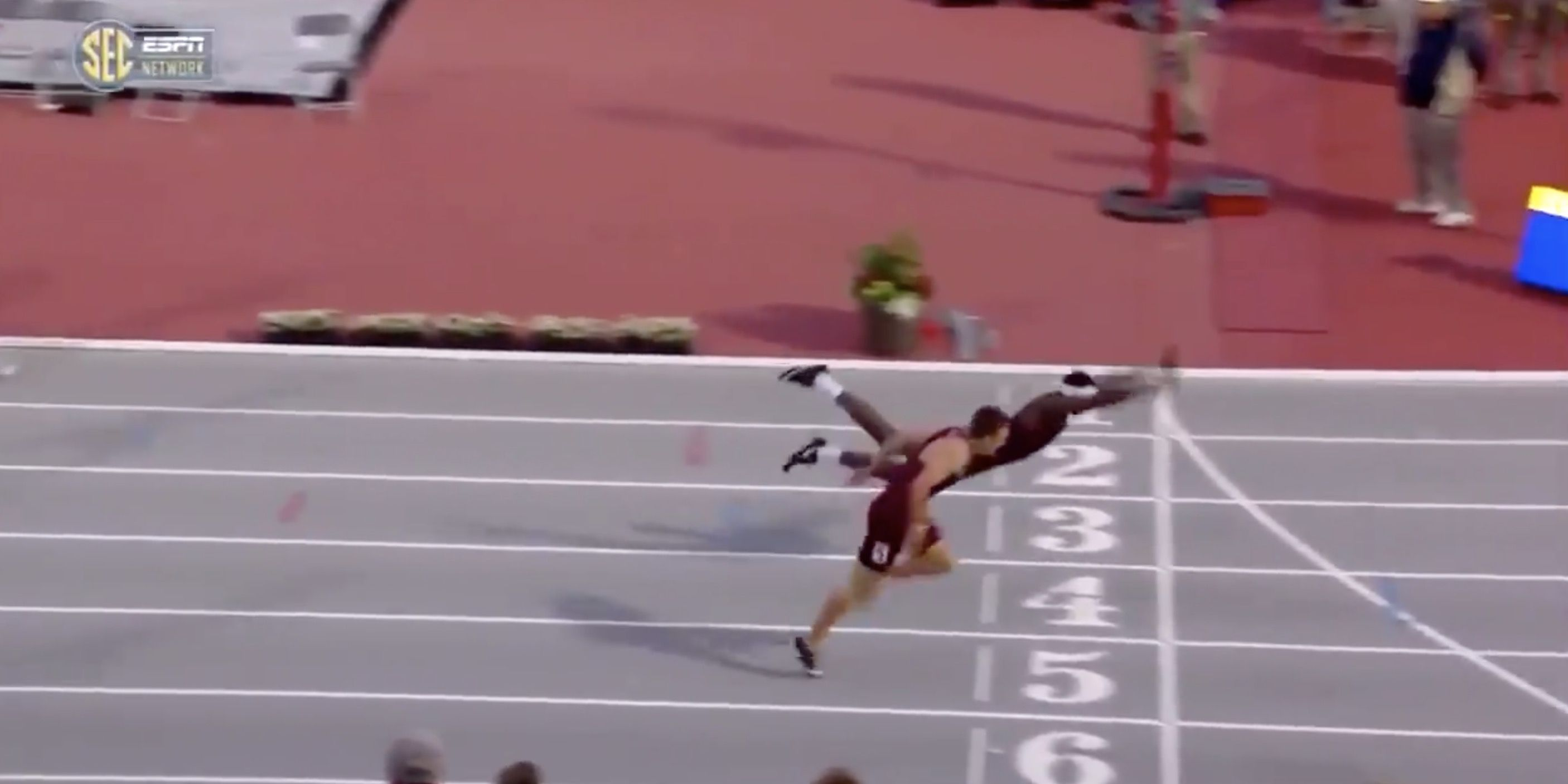 man jumps across finish line