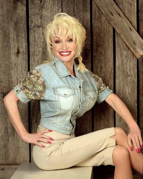 dolly parton smiling with a wood planks in the background