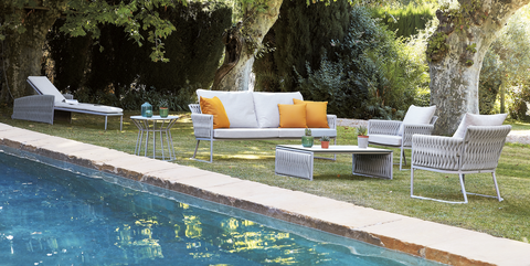 outdoor sofa, chairs, chaise and tables by a pool