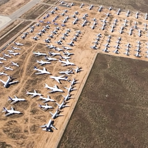 seen from above, about 100 large airplanes are parked on a brown dirt field