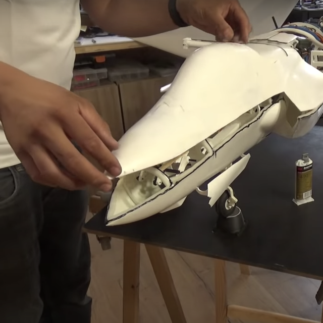 two hands carefully fitting a top piece onto a fighter jet model
