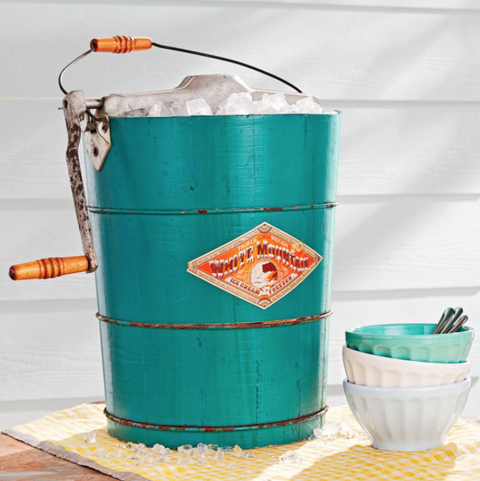 a vintage turquoise ice cream maker on an outdoor table