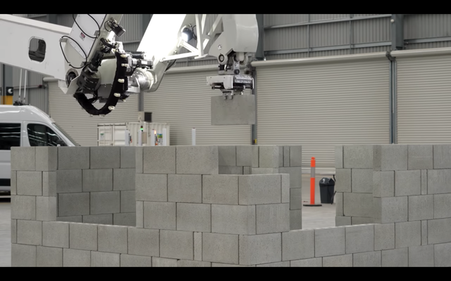 the hadrian x robot, holding a brick that's ready to place