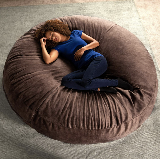 big brown bean bag chair with person laying on it