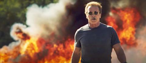 Arnold Schwarzenegger walks off like an ass from an explosion
