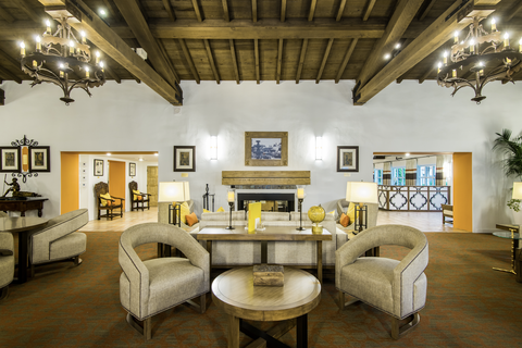 lobby of hotel fitted with beige arm chairs and wooden tables, yellow accent pieces sit on the tables with lit lamps beside wooden beams on the ceiling and chandeliers hang from there