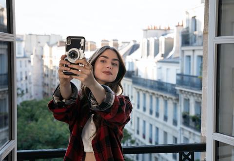 Лили Коллинз, брюнетка с европеоидной расой, стоит на балконе в Париже и делает селфи, на ее iphone есть чехол, похожий на старинную камеру