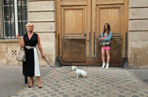 лили коллинз, брюнетка с европеоидной расой, стоит перед деревянной дверью и фотографирует белую собаку, которая какает на тротуаре. хозяйка собаки - белая женщина со светлыми волосами.