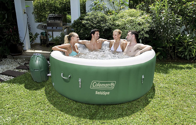 four people in the green and white inflatable hot tub on grass