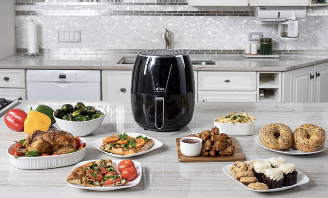 aria air fryer surrounded by dishes like turkey, bagels, chicken wings, cupcakes, pizza, and fish