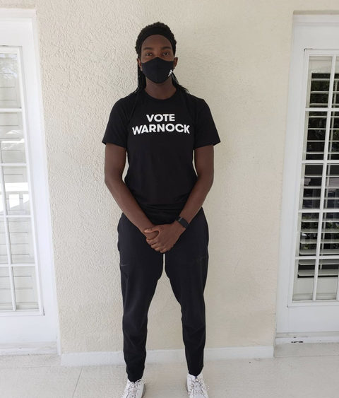 "wnba star elizabeth williams wearing a ""vote warnock"" t shirt"