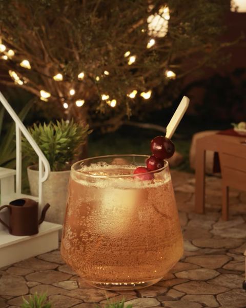 a golden cocktail in a glass with ice and cranberry garnish