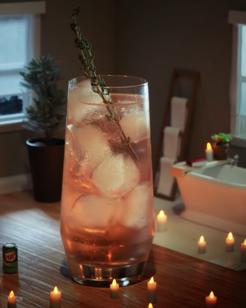 a pink cocktail with ice in a highball glass