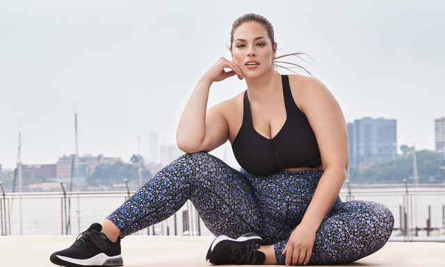 ashley graham sits on an outside dock wearing activewear from knix