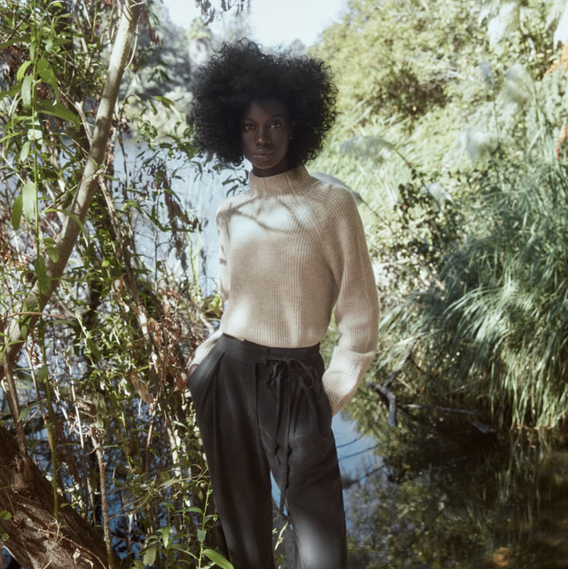 a model wears a reformation cashmere sweater in front of a forest background as part of the reformation 2021 sale