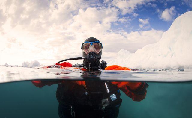 scuba diver next to an iceberg split shot