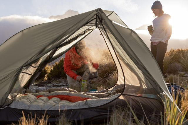 two people camping with a gray tent