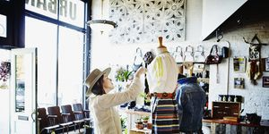 Female shop owner dressing mannequin for display