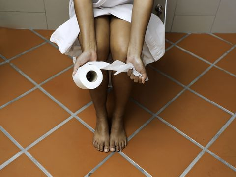 selective focus of woman hand and paper roll which she is sitting in toilet felling unhappy, diarrhea constipation,healthy concept