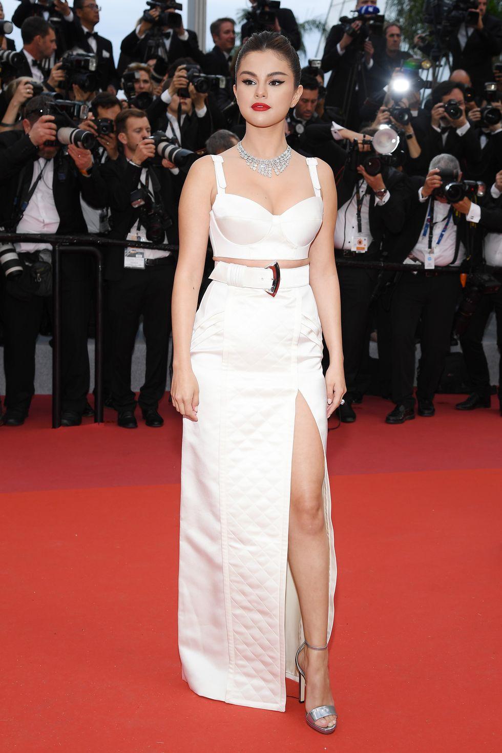 Selena pun hadir berbalut gaun seksi warna light ivory, dengan aksen high-slit dari Louis Vuitton