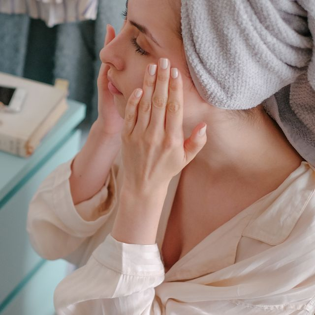 woman in towel doing skincare routine in mirror