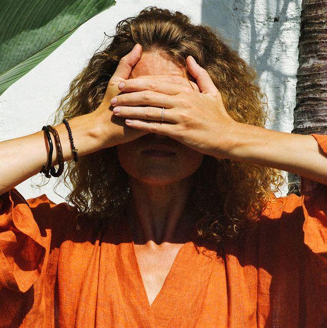 tan woman in orange dress shading her eyes from sun