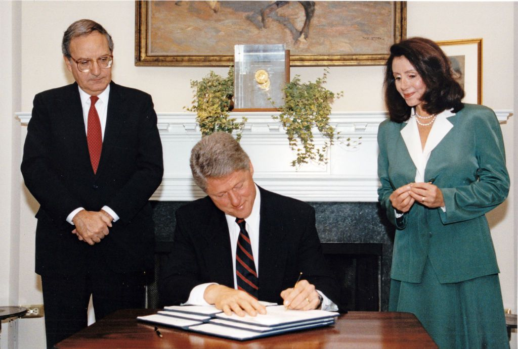 Pelosi looks on as President Bill Clinton signs an executive order.