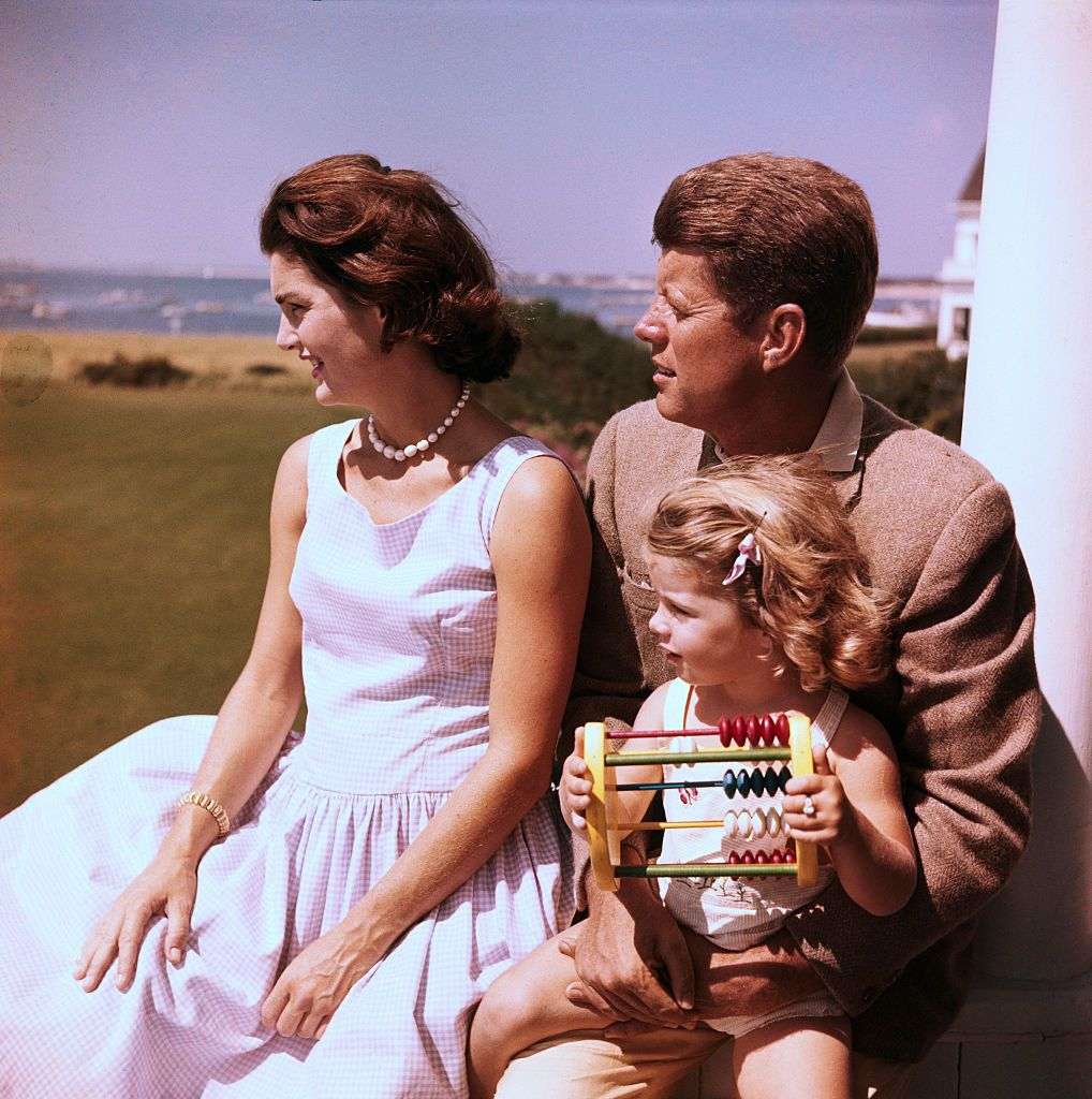 Jackie, dressed for summer in a gingham print dress and pearls, relaxes with husband JFK and daughter Caroline.