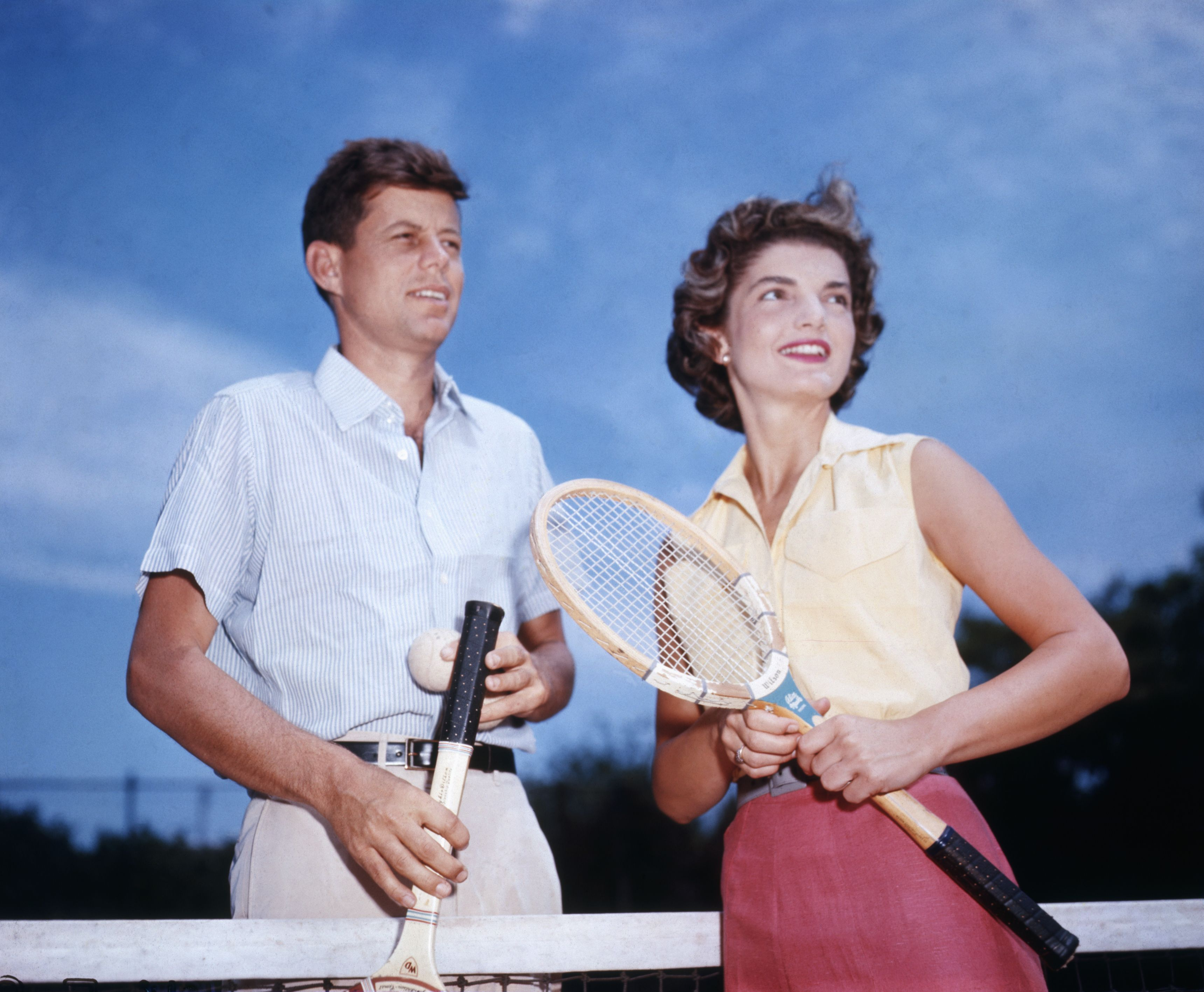 Jackie and her fiancée, John F. Kennedy, play tennis at his family's home in Hyannis Port, MA.