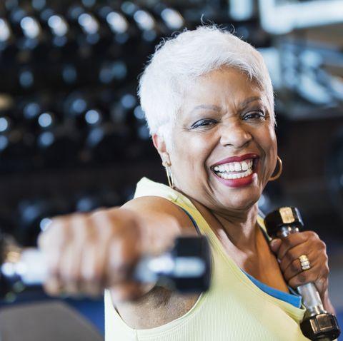 senior african american woman at gym lifting dumbbells