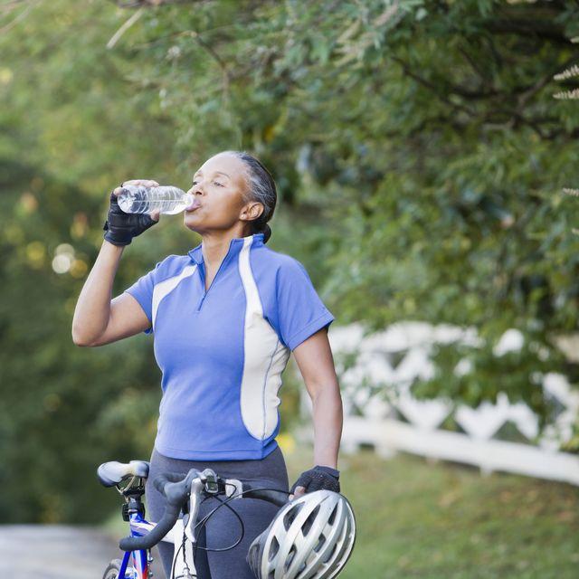 senior african female cyclist drinking water
