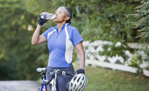 Senior African female cyclist drinking water