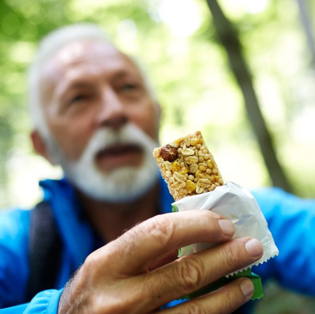 Senior backpacker outdoors having a snack