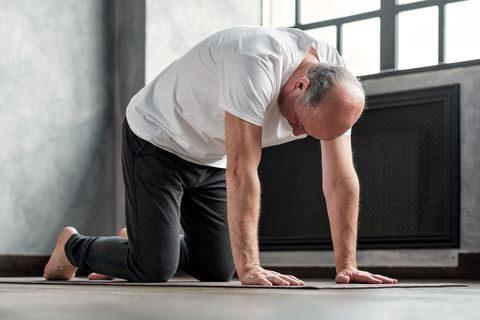 senior bald yogi men practices yoga asana marjariasana or cat cow pose