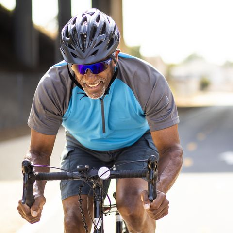 Senior Black Man Racing on a Road Bike